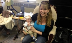 A mother holds an infant in her arm. EEG electrodes are attached and connected to a measuring device.