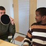 A clinician and a patient are sitting side by side. The clinician is holding a black round mat in front of his fact to hide his lips.