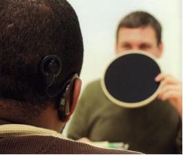 View from the back of the patient. A brown hearing aid is visible on one ear. A clinician holding a round black mat to hide his mouth is seen sitting in front of the patient.