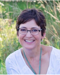 Shelley Gladden: Woman with short dark brown hair and glasses in a grasslands environment
